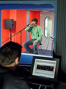 Young man singing in studio technician in foreground (thumbnail)