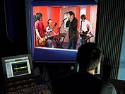 Band in recording studio technician in foreground