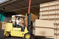 Side view of male worker operating forklift vehicle