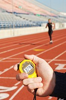 Man holding stopwatch close up of hand timing runner on running track (thumbnail)