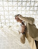 Businessman using mobile phone outdoors low angle view