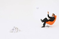 Businessman throwing piece of crumpled paper on pile (thumbnail)