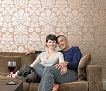 Smiling couple relaxing on sofa in living room portrait