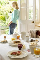 Woman With Tea standing in doorway hand on hip After Breakfast
