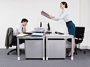 Businesswoman passing off work to male colleague in office