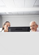 Two office workers looking at computer in office cubicle