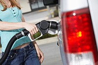 Young woman filling car with gas at gas station mid section (thumbnail)