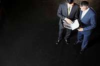 Elevated view of two businessmen reading documents against dark background