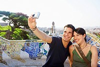 Smiling couple taking photo of themselves portrait (thumbnail)