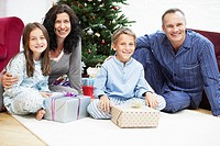Happy Family in Front of Christmas Tree portrait (thumbnail)