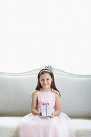 Smiling girl in tutu sitting on sofa holding gift portrait