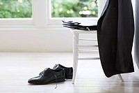 Clothing of businessman on chair and floor