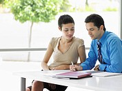 Businessman and woman at office table going over document information
