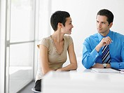 Businessman and businesswoman at office table in discussion