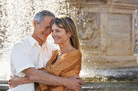 Middle_aged couple hugging by fountain Rome Italy close up
