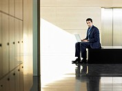 Businessman sitting on bench by elevator using laptop