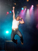 Young Man Singing and jumping on stage at concert low angle view