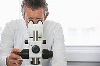 Male lab worker adjusting microscope