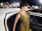 Woman in evening wear getting out of limousine in front of fans and paparazzi (thumbnail)