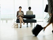Businesswoman sitting on bench in airport reading newspaper