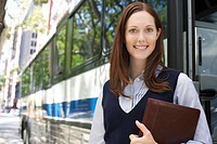 Young woman holding portfolio by bus portrait