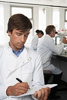 Lab Worker writing colleagues behind