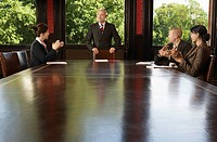 Businesspeople around boardroom table applauding man (thumbnail)