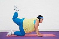 Overweight Woman on floor doing aerobic stretches