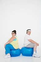 Overweight man and woman sitting back to back on exercise balls portrait (thumbnail)