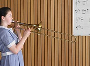 High school girl playing trombone in class side view (thumbnail)