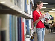 Teenage student reading text books by library shelf (thumbnail)