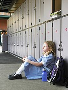 Elementary schoolgirl sitting on floor against school lockers (thumbnail)