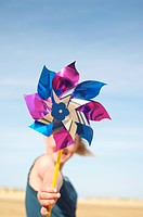 Girl standing on beach holding pinwheel close up of pinwheel (thumbnail)