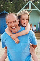 Father giving daughter piggyback on beach portrait