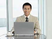 Businessman sitting at table working on laptop portrait