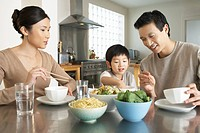 Young parents watching son stick hand in bowl at kitchen table during meal