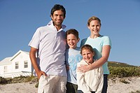 Family standing on beach smiling beach house behind (thumbnail)