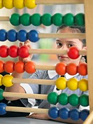 Elementary schoolgirl looking through abacus sitting in classroom (thumbnail)