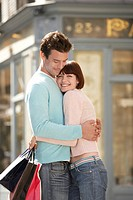 Couple with shopping bags embracing on street corner