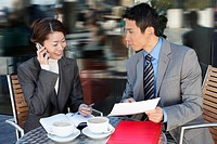 Businesspeople Meeting at outdoor Cafe talking on phone reviewing documents