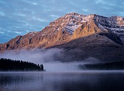 Rocky mountain fog over lake sunset