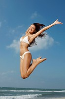 Woman jumping on beach mid_air
