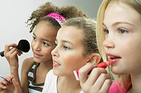 Girls standing side by side putting on make-up and lip gloss (thumbnail)