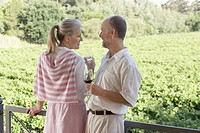 Mature couple on terrace holding wine glasses