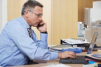 Businessman talking on mobile phone using laptop in office (thumbnail)
