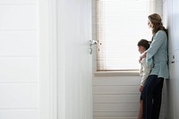 Mother and daughter standing looking out of window (thumbnail)