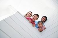 Family peering over white wall view from below