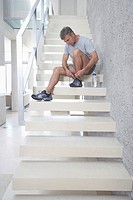 Mid_adult man sitting on stairs tying shoes