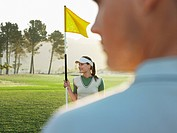 Young female golfer holding flag defocused man in foreground