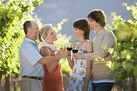 Family toasting in vineyard